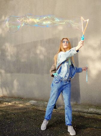 Girl in jeans clothes and dark glasses inflates a long soap bubble on a gray concrete wall Banco de Imagens