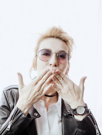 A beautiful girl in sunglasses sends an air kiss. Shooting high key 版權商用圖片