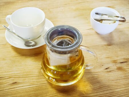 A transparent glass teapot with tea next to a vase with sugar and a clean cup stand on a wooden surface. Tea party