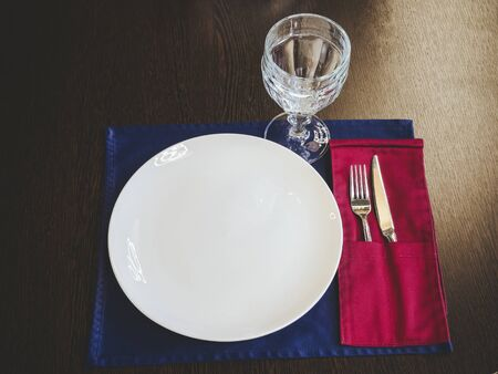 White ceramic plate with a glass and silverware lie on a napkin on a wooden surface. Table setting Foto de archivo
