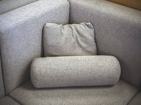 A closeup photo of a fragment of a soft gray fabric sofa with a square and cylindrical pillow. Corner view