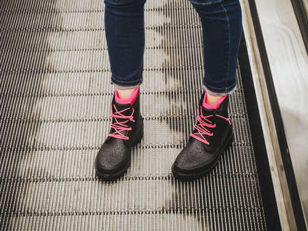 Female legs in blue jeans and black wet rubber boots with pink laces stand on the escalator