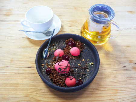 A plate with a pink dessert, a transparent jug of tea and a clean cup on a saucer on a wooden counter Stock Photo