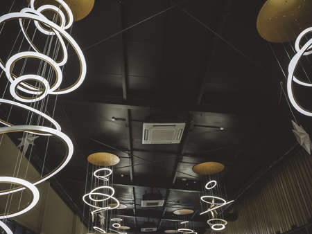 Black loft style ceiling with bright LED lights in the shape of rings of different sizes and with square air conditioning in the middle of it 版權商用圖片