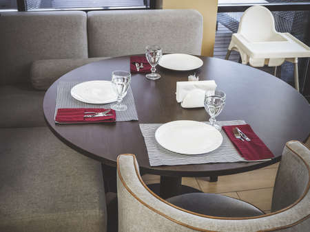 On a round table are cutlery for three people, next to a soft gray sofa and armchair Stock Photo