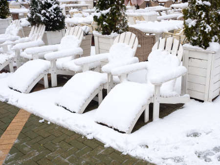 Wooden white sun chairs stand in a row strewn with snow