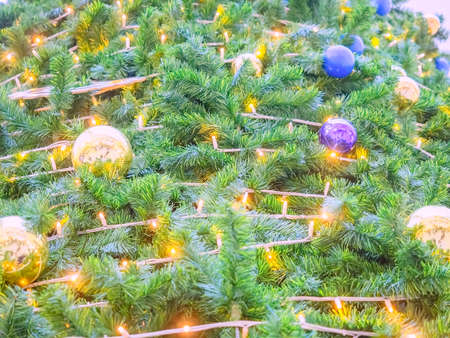 A lush Christmas tree with a luminous garland, blue and gold balls. Full screen photo
