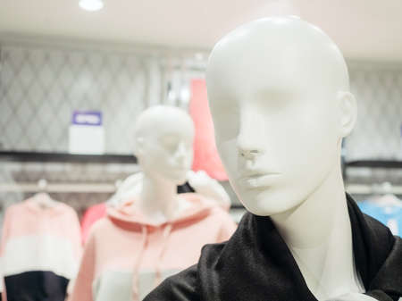 White mannequin head on blurred background of shop and other mannequin