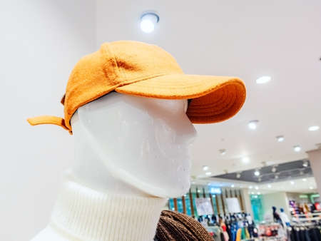 Head of a male mannequin in a red cap on the background of the store