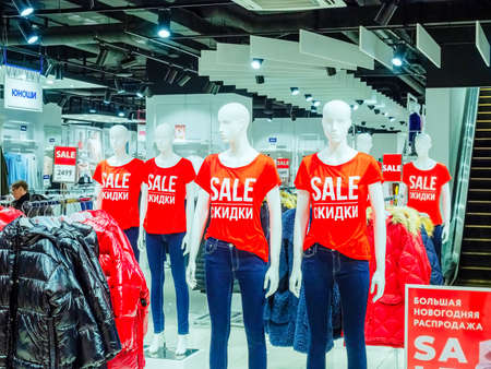 Sochi, Russia - 14 December 2019. White mannequins in red T-shirts with SALE inscription stand in a row inside the store