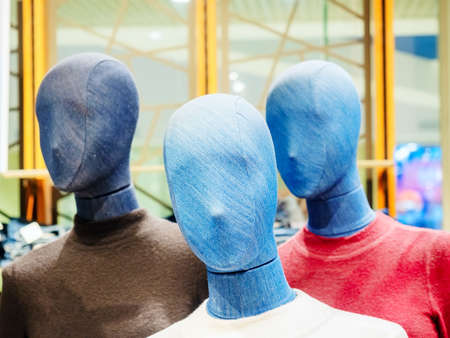 Mannequins with denim faces in colored turtlenecks in a store. Focus to the foreground