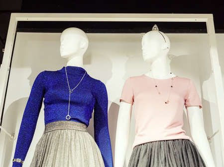 Two identical female mannequins in blue and pink blouses stand turning their heads to the side