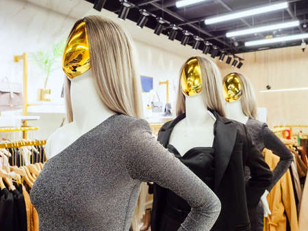 Female abstract mannequins with golden faces in evening wear stand in boutique