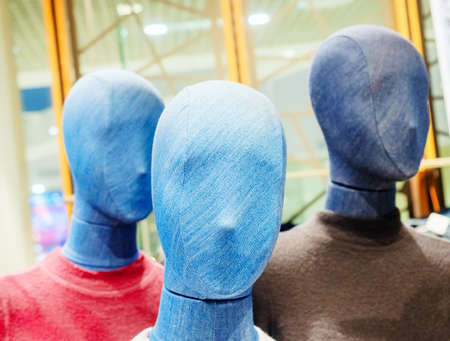 Mannequin covered with blue denim on the background of similar mannequins in the store