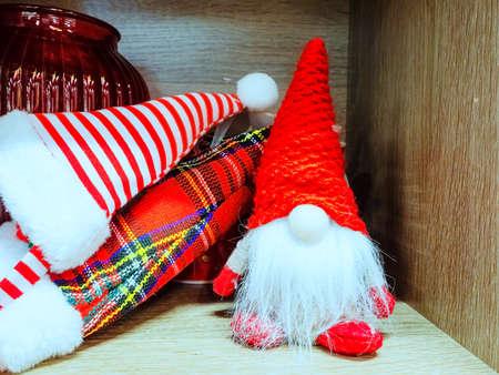 Plush toy gnome on the shelf next to the striped and checkered caps Zdjęcie Seryjne