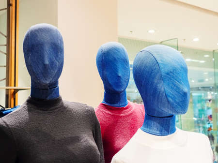 Mannequins covered in denim in colored turtlenecks in a store.