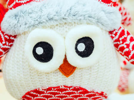 Cute knitted toy white owl with big eyes. Close-up photo