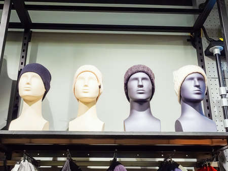 Male and female gray and white mannequin heads in knitted hats stand on a shelf