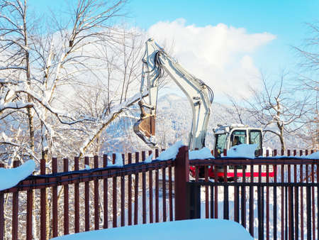 An excavator behind a fence works in a mountain valley on a clear winter day