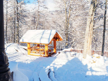 View of a wooden gazebo standing on a snow-covered meadow among trees in the mountains 版權商用圖片