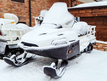 An ATV covered with snow stands near a house with a stone wall