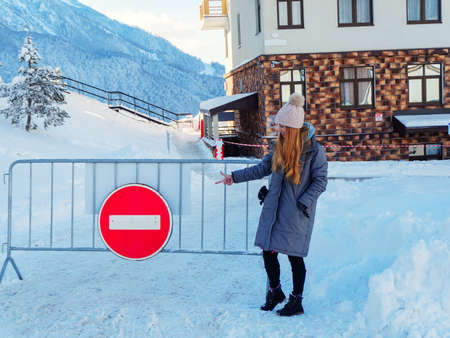 The girl points her finger at a red round sign hanging on the barrier on a winter day. No entry