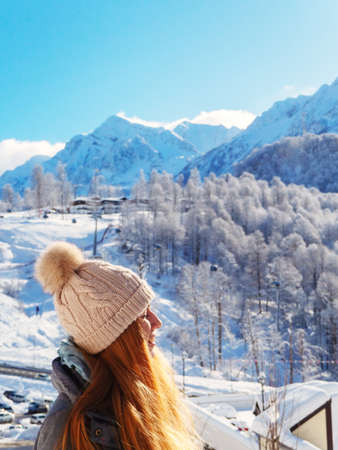 Profile of a red-haired girl in a hat with a bubo on the background of a winter mountain landscape