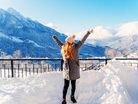 A joyful girl stands with her arms outstretched against the backdrop of snowy mountains