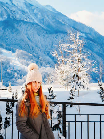 Redhaired smiling girl stands at the fence against the background of high snow-capped mountains Reklamní fotografie