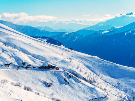 Snowy ski slopes in the background of mountain ranges and blue sky with clouds 版權商用圖片