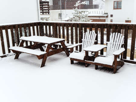 Two wooden chairs and a table with benches stand on a snow-covered veranda under a snowfall