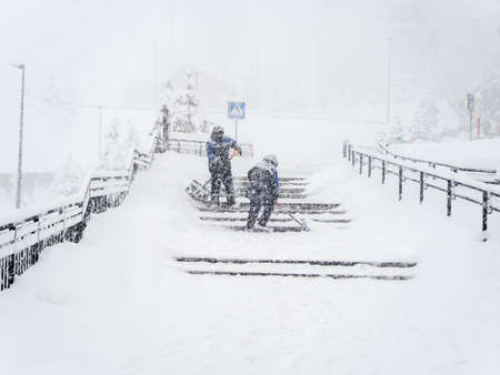 Workers shovel snow from steps outside during heavy snow