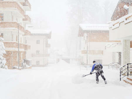 A worker clears snow among cottages on a foggy day during a blizzard