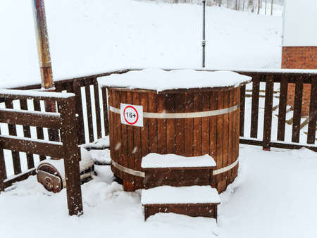 Wooden furaco baptismal font strewn with snow stands on a terrace with a wooden fence on a snowy winter day