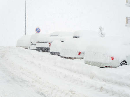 Snow-covered road with cars parked along it covered with snow during winter cold and blizzard