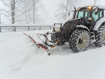 Snow plow tractor clears snowy road during heavy blizzard