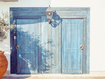 Light blue wooden doors with round golden door handles and a lantern in between