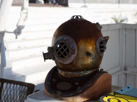 Decorative metal diving helmet on a rack against a background of white wooden walls Stockfoto
