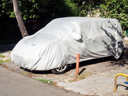 Car covered with a cloth cape in a parking space lit by the sun under the trees in the yard