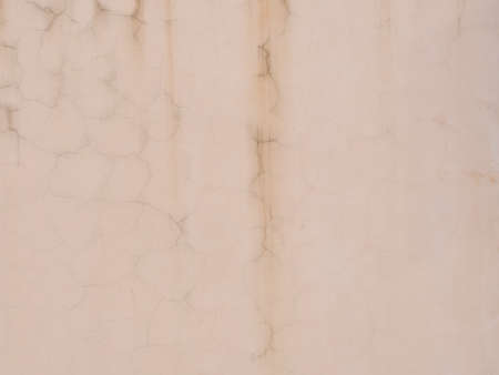 Pink wall with streaks of cracks and dark smudges. Texture not seamless
