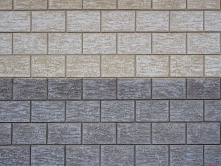 Wall cladding in rough gray and beige tiles imitating masonry.