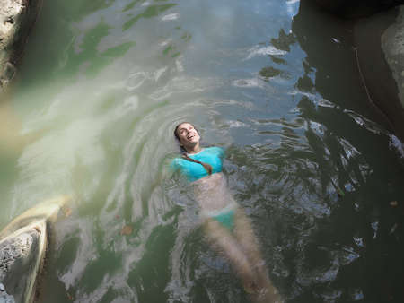 Smiling girl with face illuminated by the sun lies in the muddy water of a rocky gorge 版權商用圖片