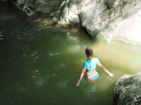 A girl in a blue swimsuit walks into the muddy green water of a rocky gorge