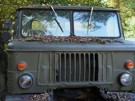 An old abandoned military truck with broken glass stands strewn with dry foliage surrounded by green trees