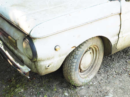 Fragment of an old dirty white car standing on the ground