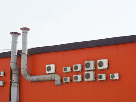 A fragment of an orange building with many air conditioners hanging on the wall and two ventilation pipes