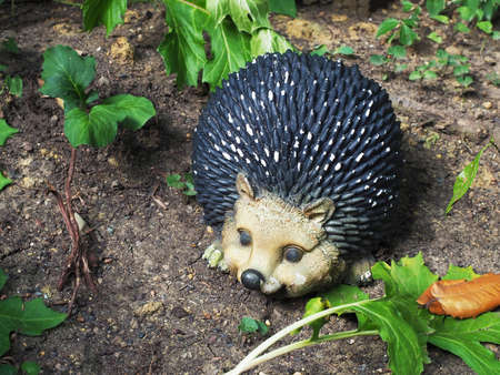 Decorative figurine hedgehog on the ground among green plants. Garden decor