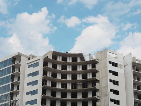 Unfinished gray building in modern style with blue sky and clouds background 版權商用圖片