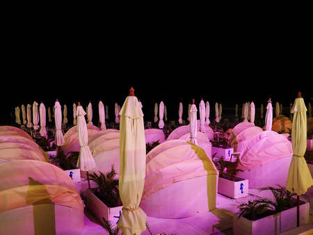Semicircular beach sofas with a canopy and umbrellas between them stand in a recreation area on the seashore at night in pink lighting