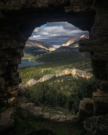 A beautiful landscape formed by mountains, forests, a lake, & a dramatic sky in Catalunya, spain 写真素材